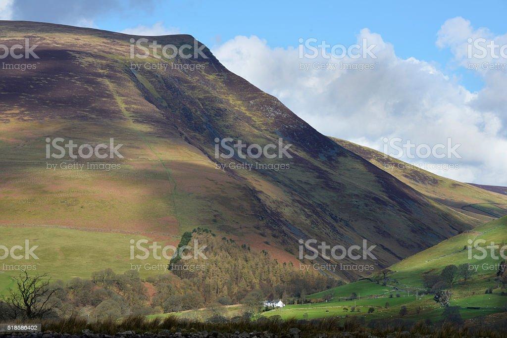 White Farmhouse Against Mountain Backdrop stock photo