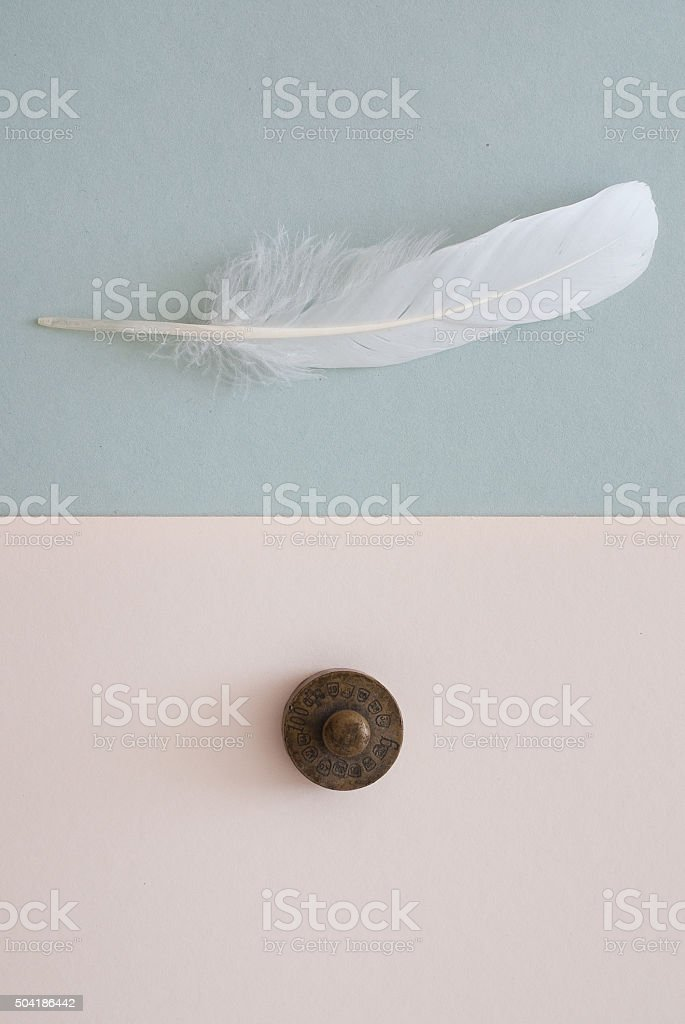 white feather and weight on grey paper background stock photo