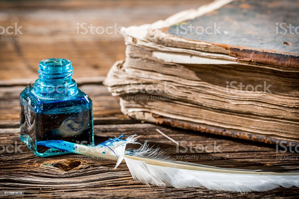 White feather on blue inkwell and old book stock photo