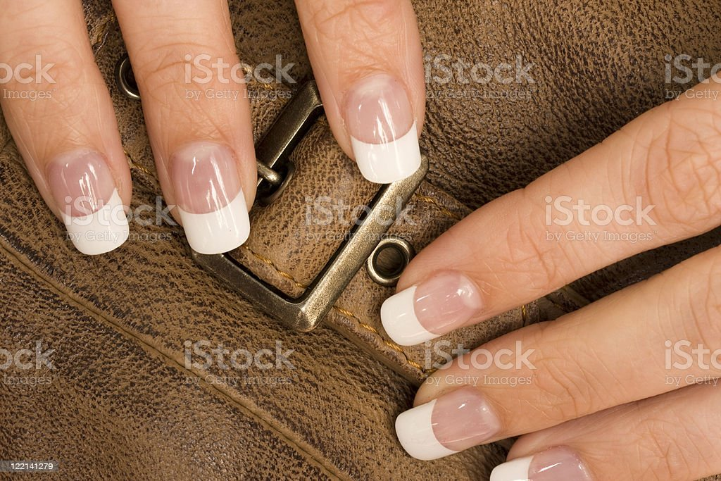 White female fingers closing a leather strap stock photo