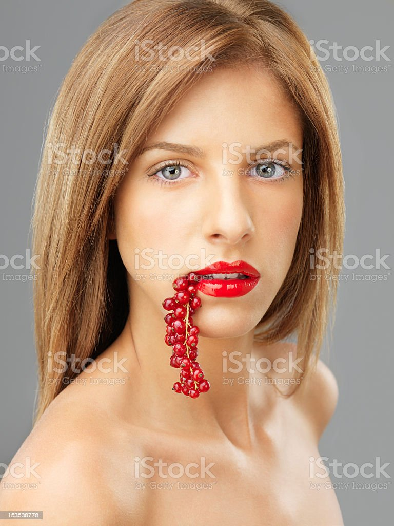 white female portrait bitting a redcurrants bunch royalty-free stock photo