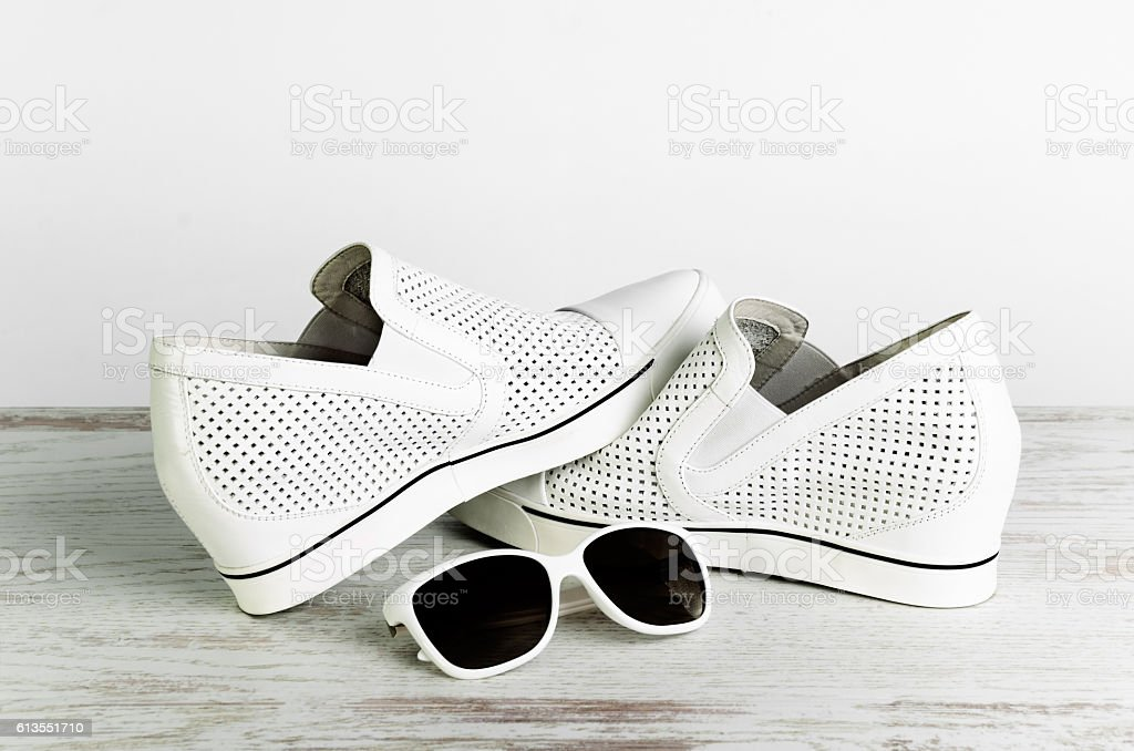 White female shoes and sun glasses  on a light background stock photo