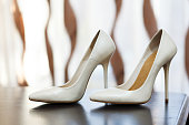 White female shoes with high heels standing on a table