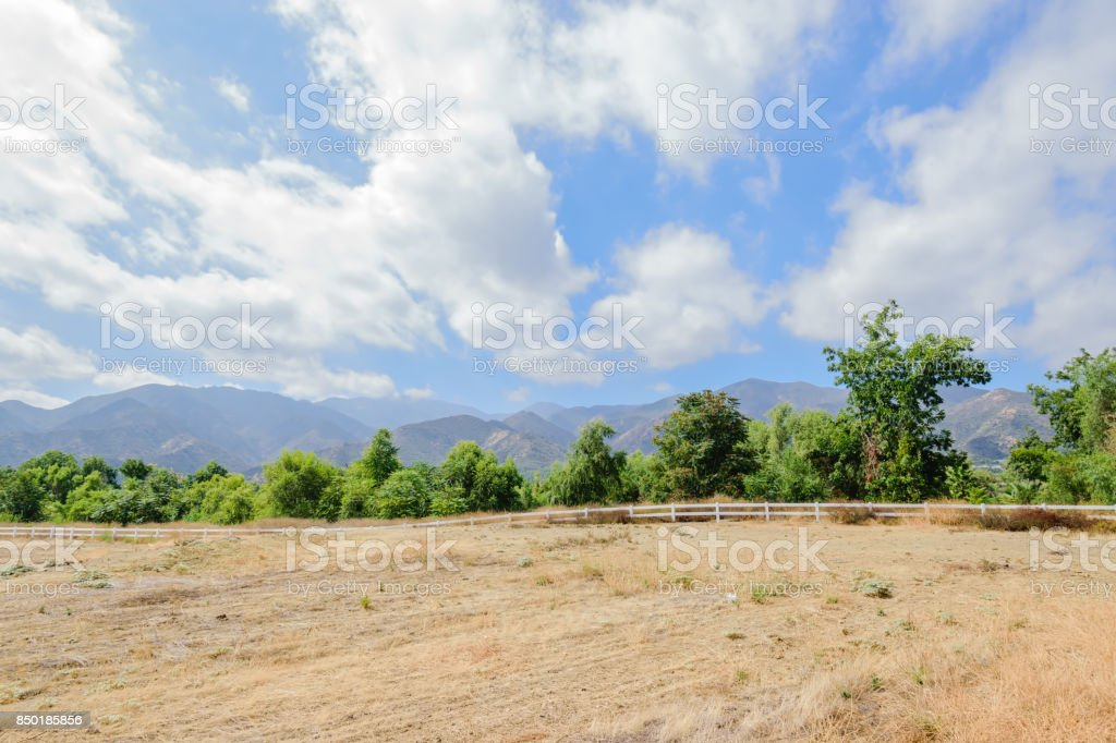 White fence lines dry grass stock photo