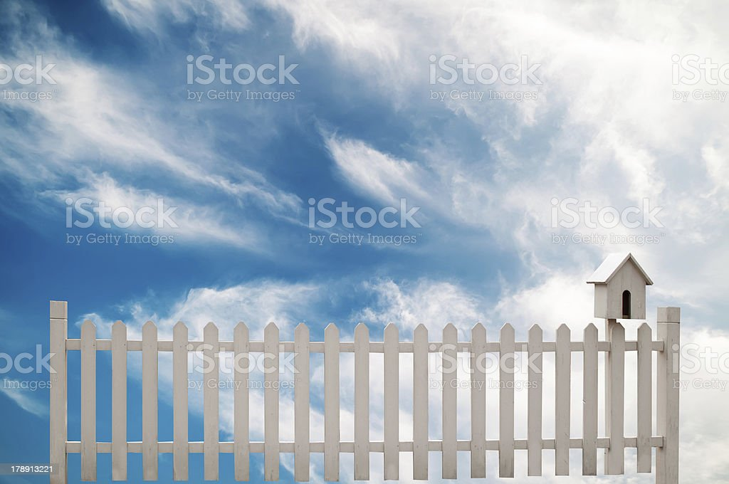 white fence with bird house and blue sky royalty-free stock photo