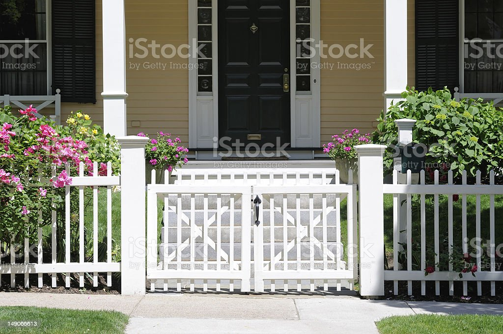 White fence with gate over a garden and a house's front door stock photo