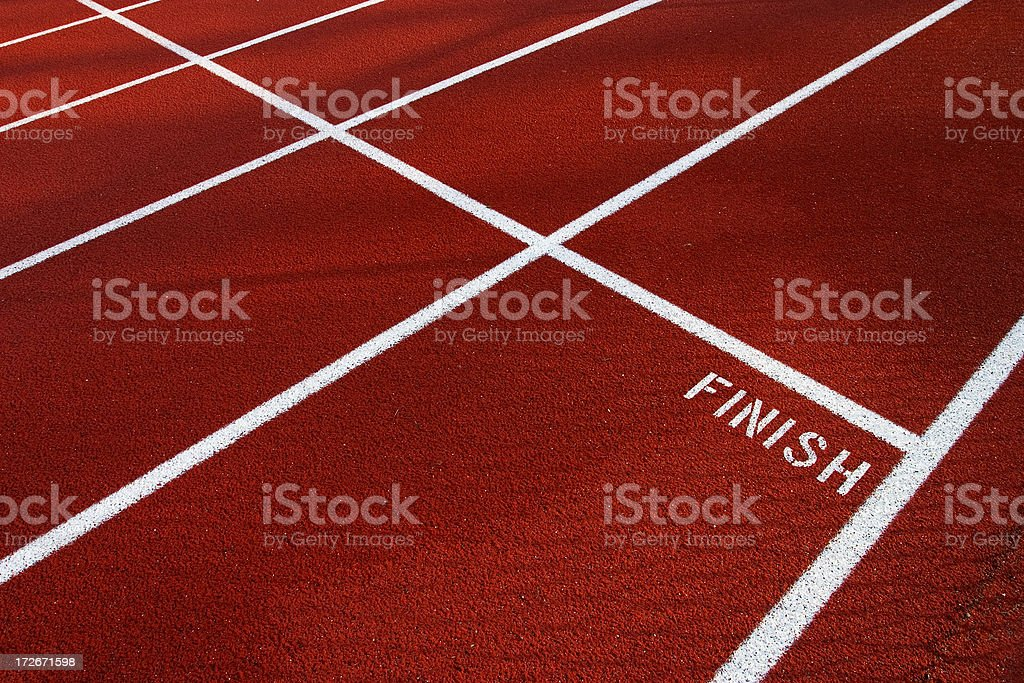 White finish line on red running track stock photo