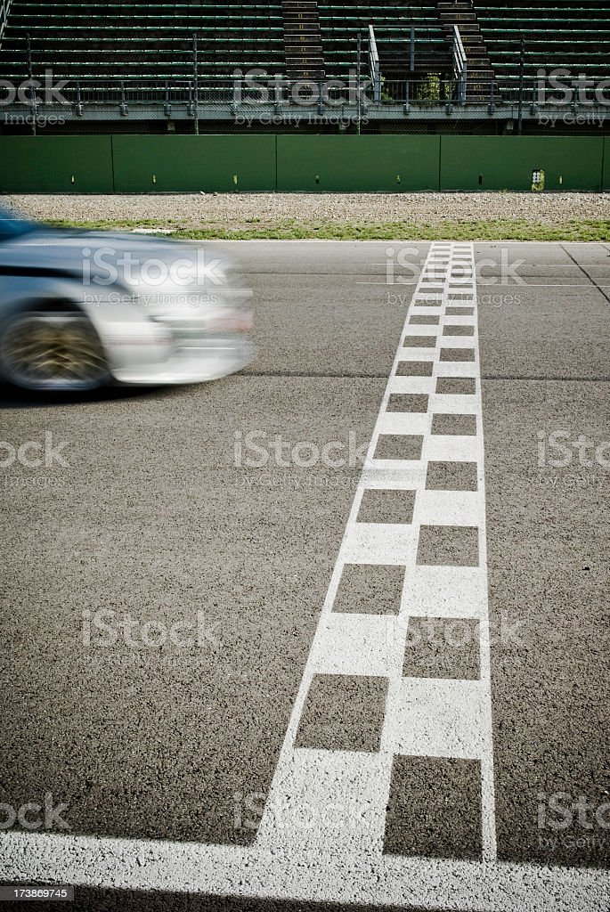 White finish line with car nearly crossing it on road stock photo