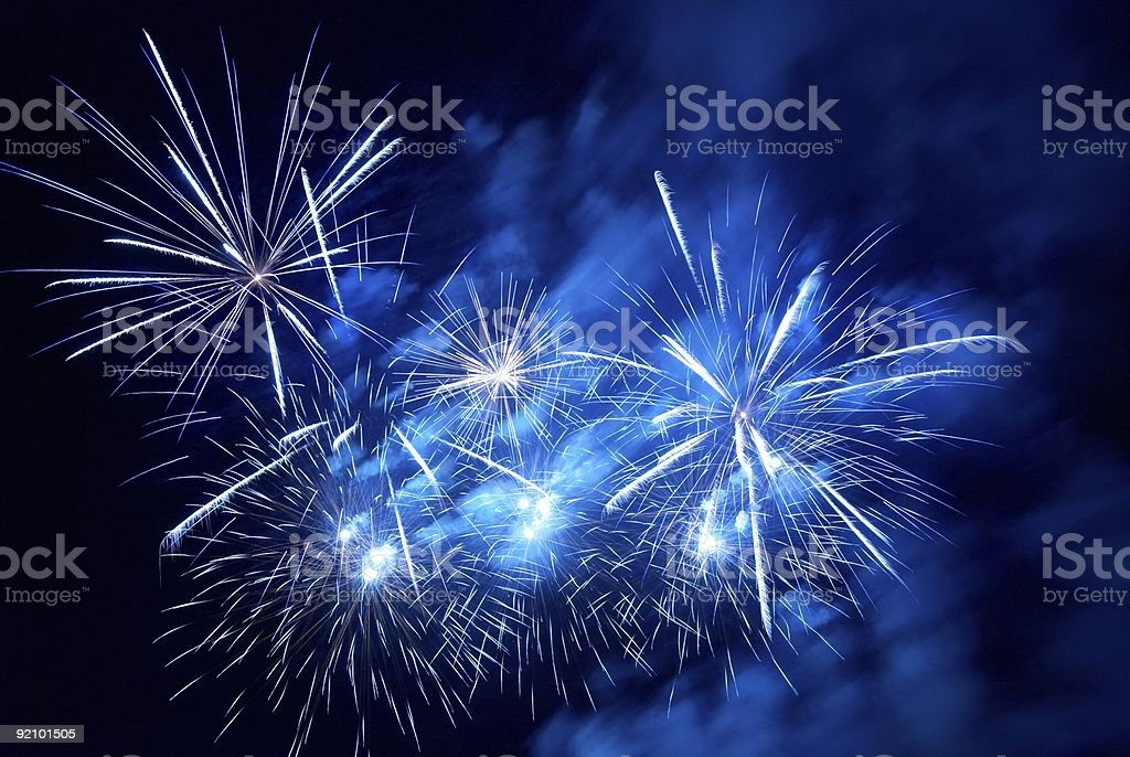 White fireworks on a black and blue background royalty-free stock photo
