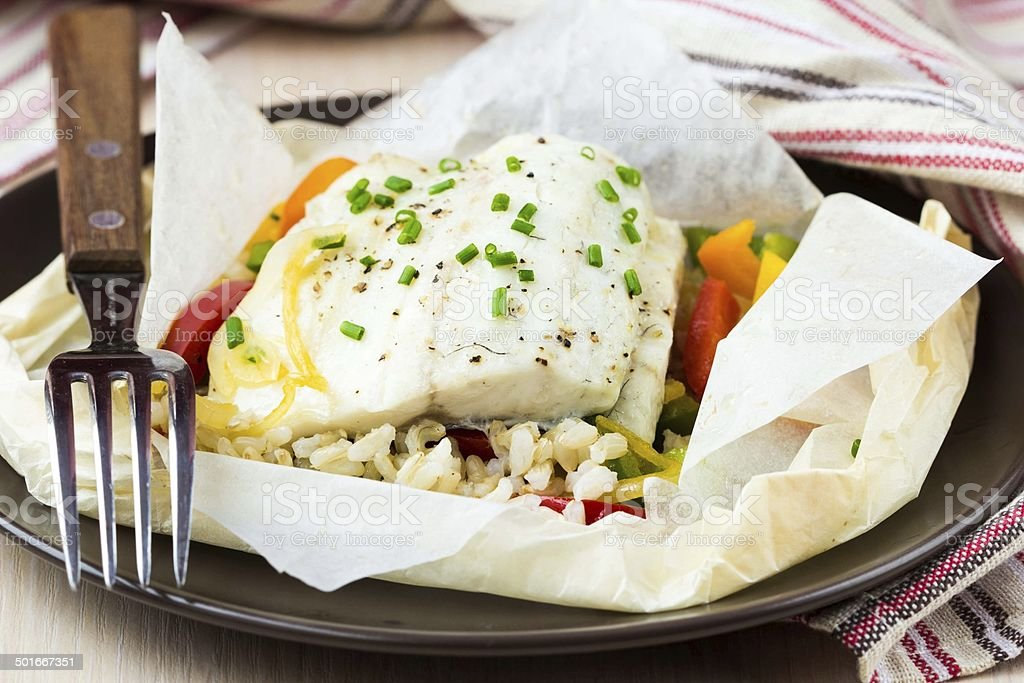 White fish fillet baked in paper, parchment with rice, pepper stock photo