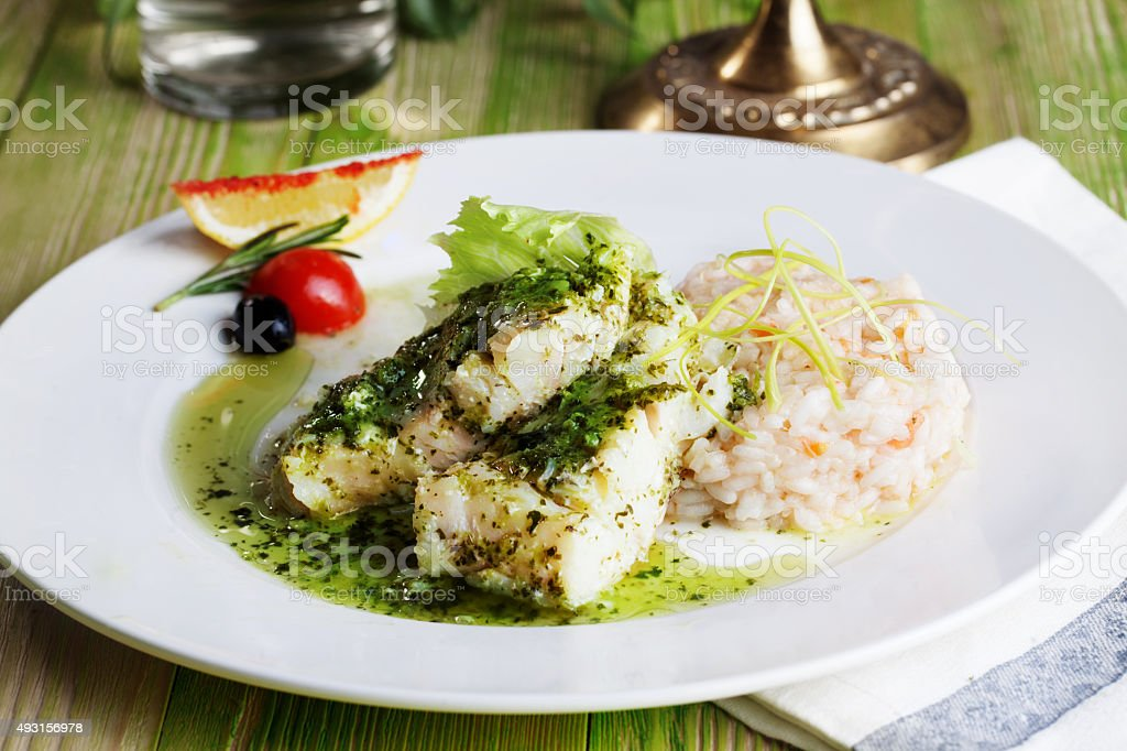 white fish with pesto sauce and meat plate in a stock photo