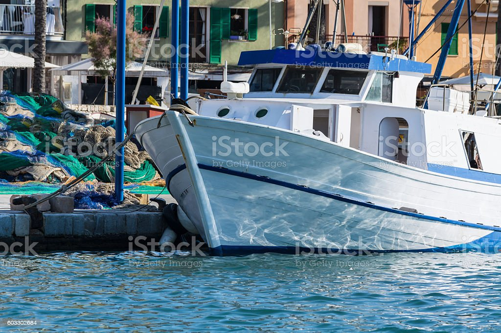 White fishing boat or trawler in the harbor stock photo