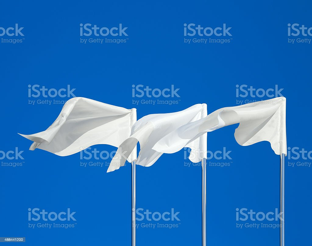 White flags against the blue sky stock photo