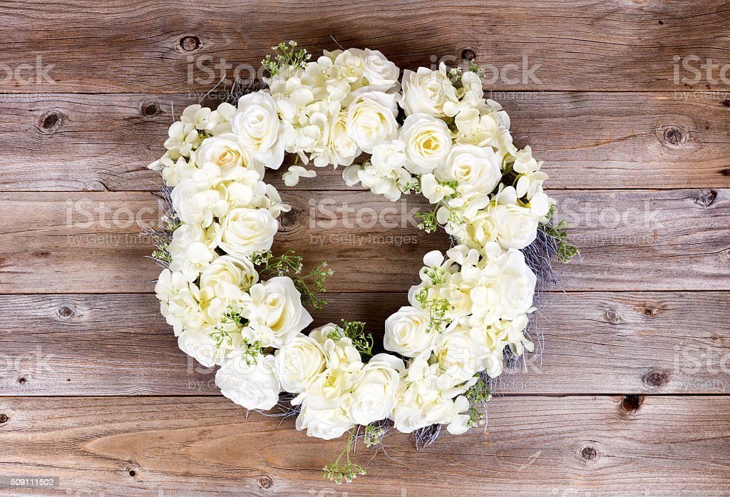 White flowers forming wreath on rustic wooden planks stock photo