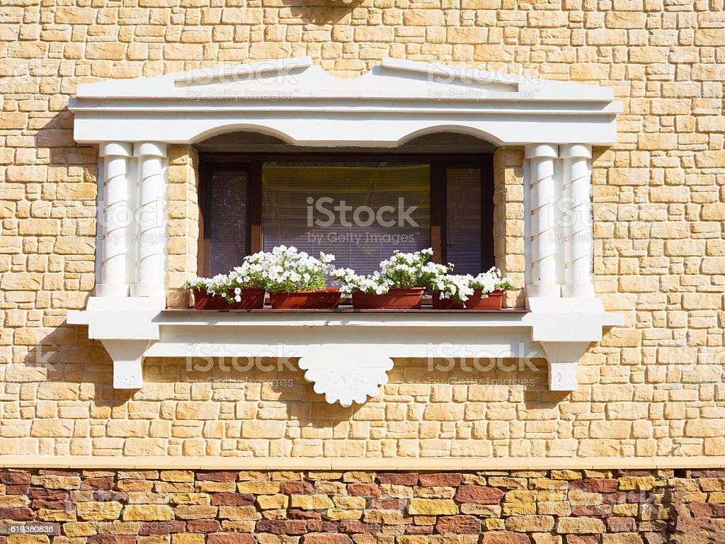 White flowers hangs on the window of home in ancient stock photo