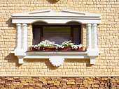 White flowers hangs on the window of home in ancient