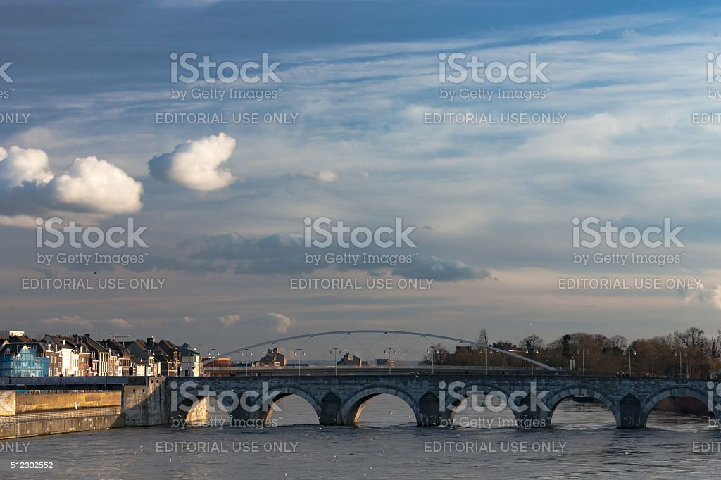 white fluffy clouds over the bridges of maastricht blue skies stock photo