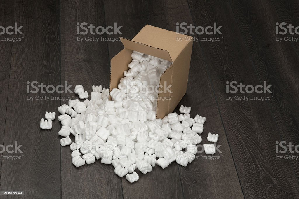 White foam pellets from cardboard container. stock photo