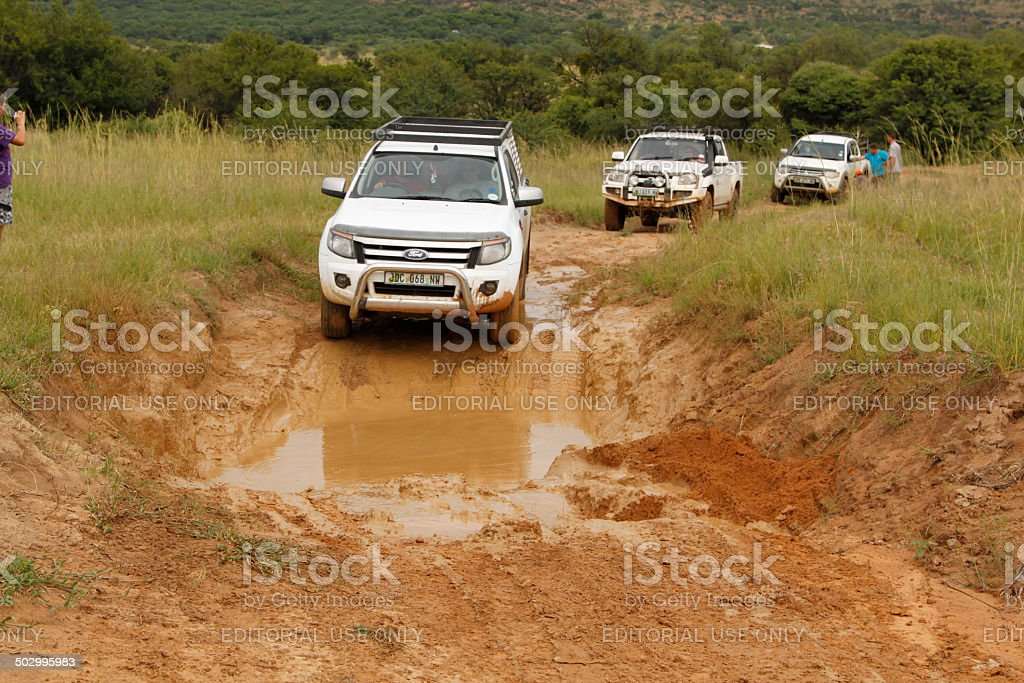 White Ford Ranger XLS with Silver Canopy crossing mud obstacle stock photo