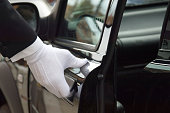 White formal gloved uniformed hand opening car door