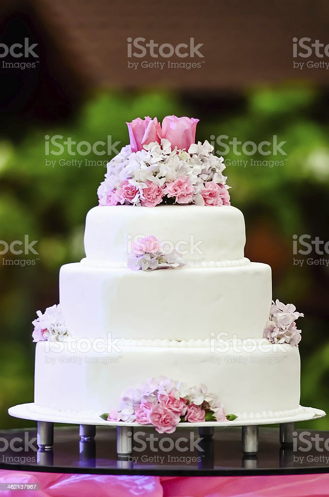 White four tiered wedding cake on table stock photo