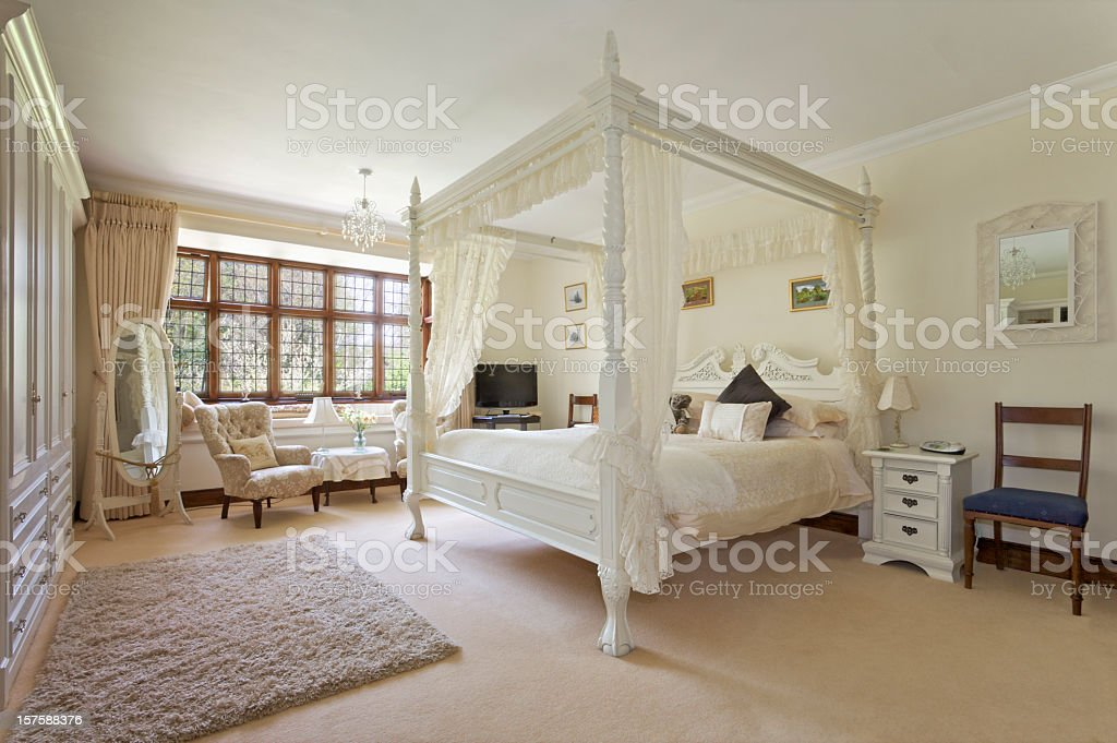 White four-poster bed in large neutral-colored bedroom stock photo