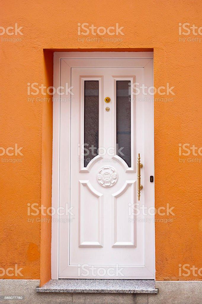 White front door in orange painted facade. stock photo