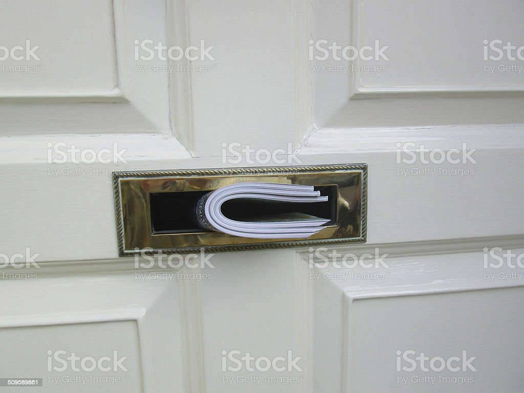 White front door, wooden panels, magazines pushed through brass letterbox stock photo