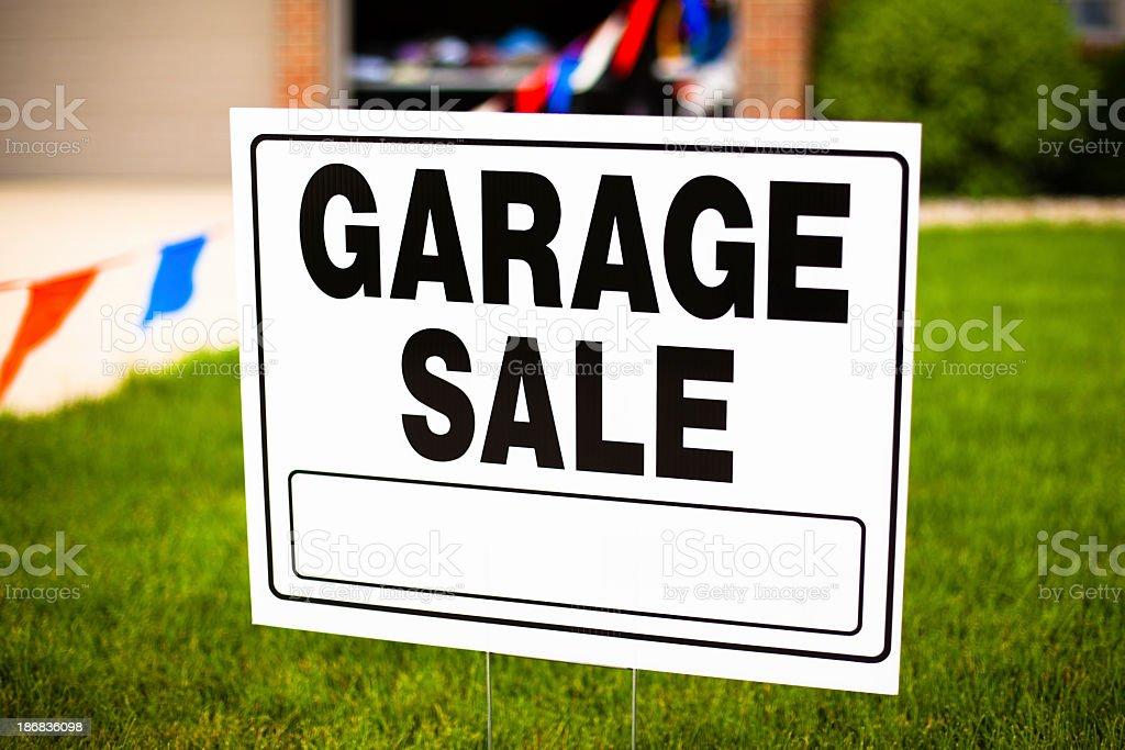 White garage sale sign on grassy lawn  stock photo