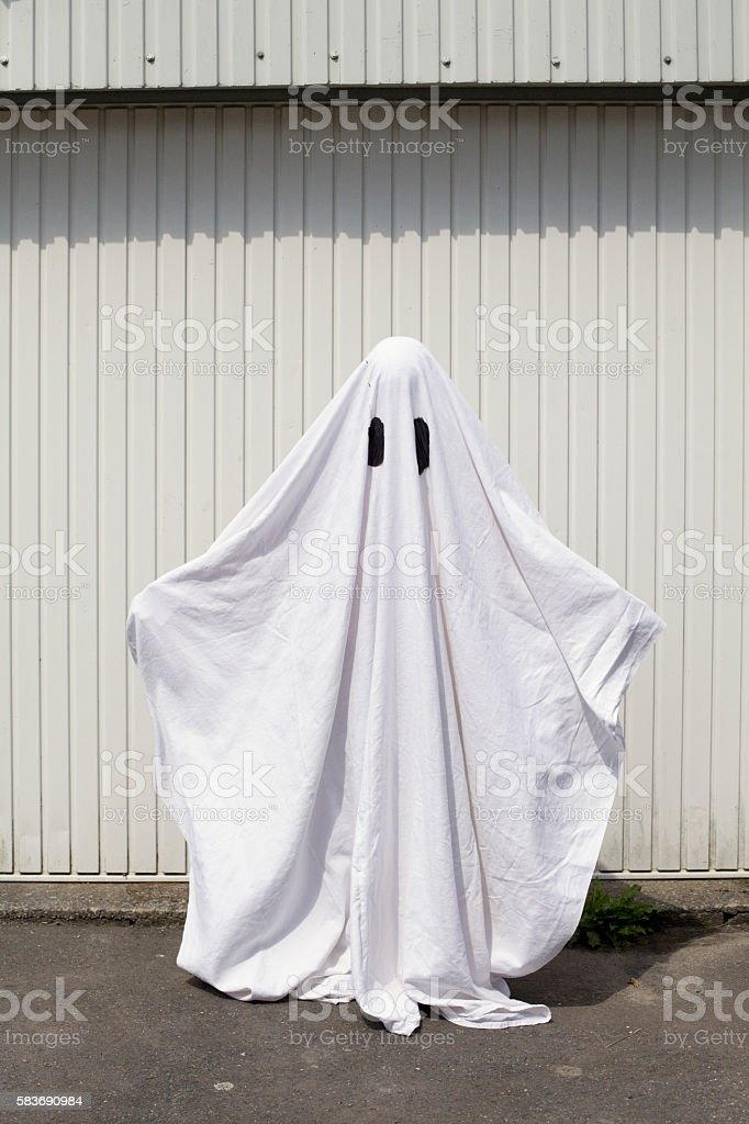 white ghost in front of a garage door stock photo