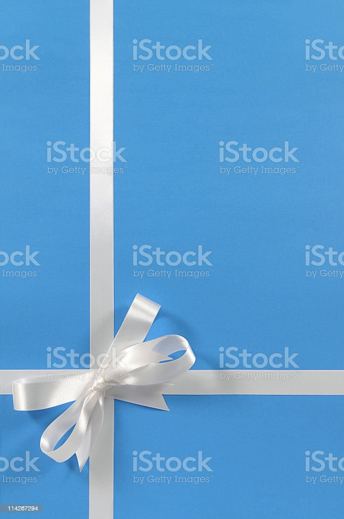 White gift ribbon on blue paper royalty-free stock photo