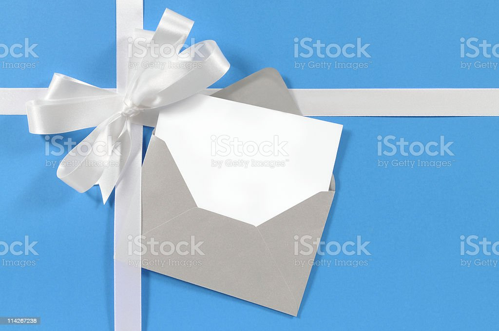 White gift ribbon on blue paper with blank card royalty-free stock photo