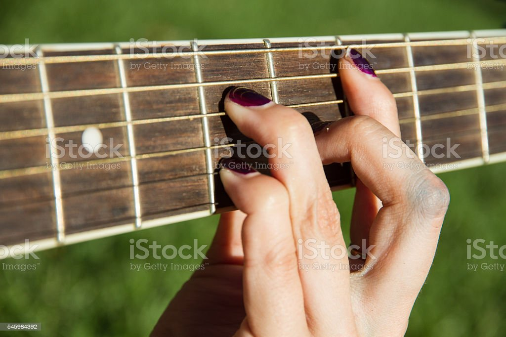 White girl holding the neck of the guitar. stock photo
