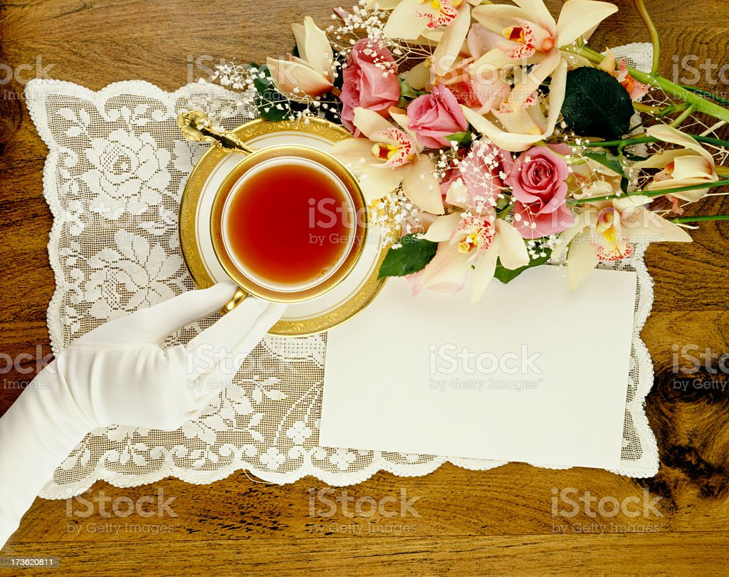 White gloved hand holding ornate tea cup by fresh flowers royalty-free stock photo