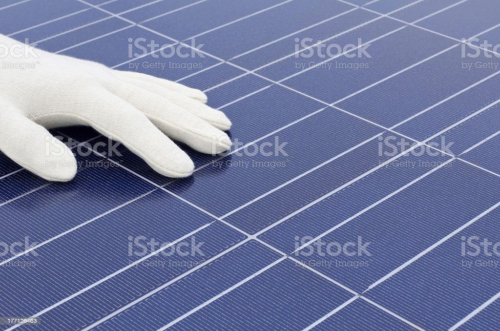White gloved hand in front of solar cells royalty-free stock photo