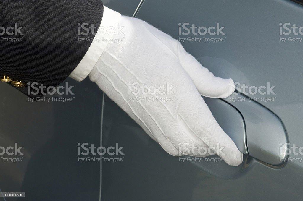 White gloved hand of chauffeur / doorman on car door stock photo