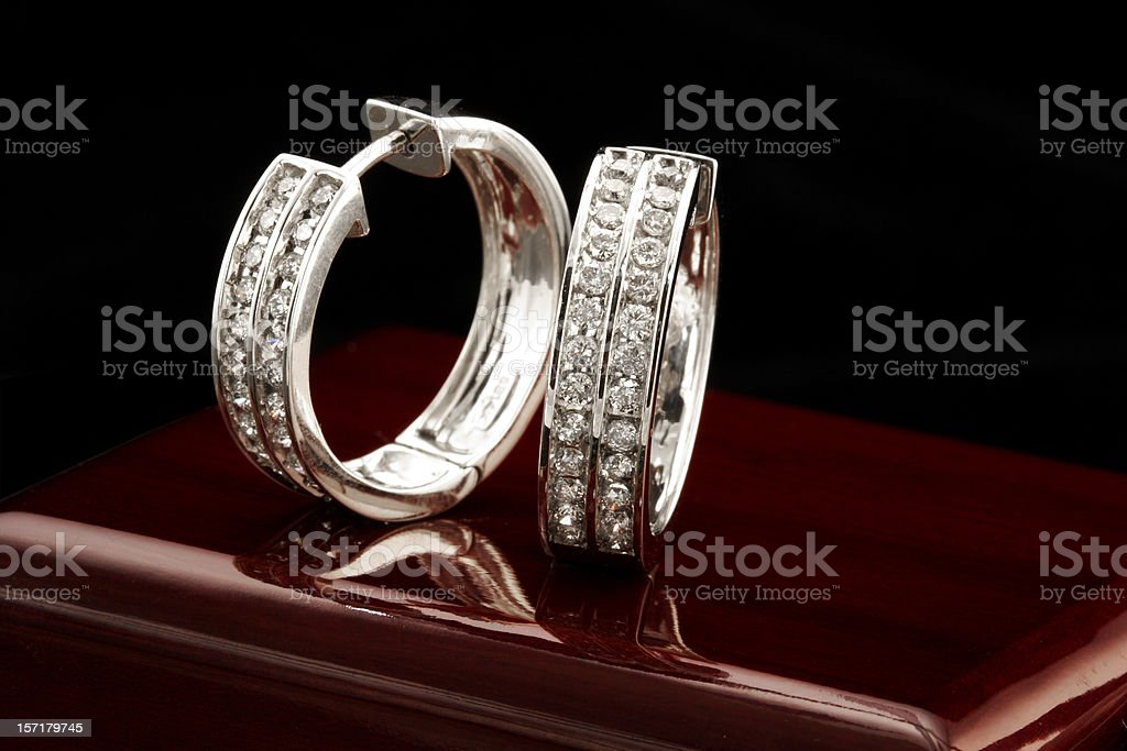 White gold diamond earrings on shiny surface royalty-free stock photo