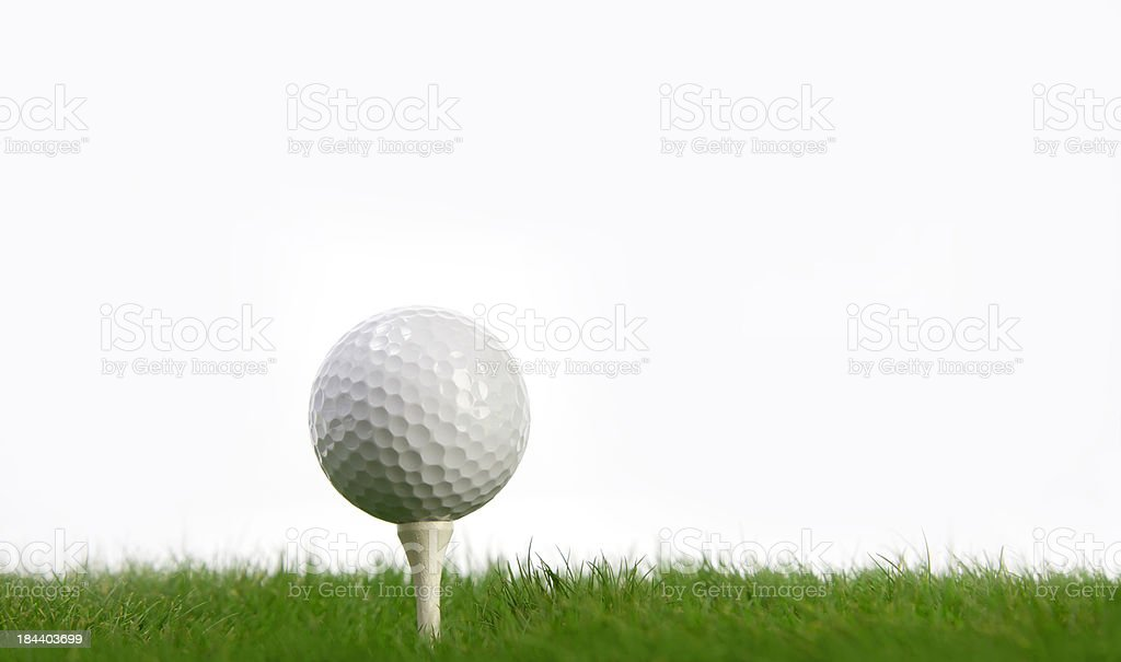 White Golf Ball and tee on green grass stock photo