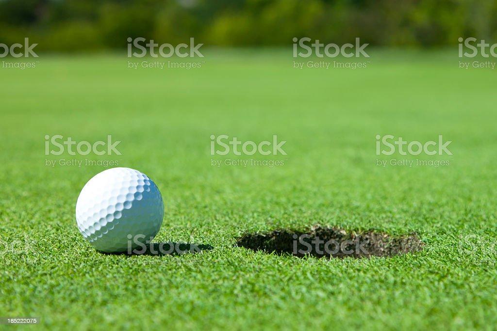 White golf ball stood next to a hole stock photo