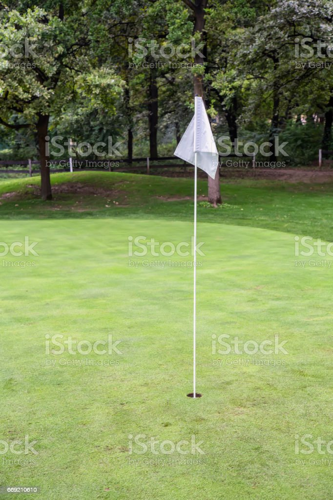 White golf flag on a field stock photo