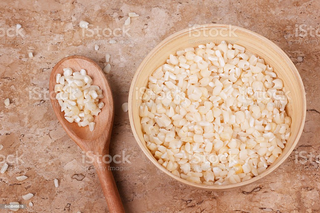 White grated corn kernels in wooden bowl stock photo