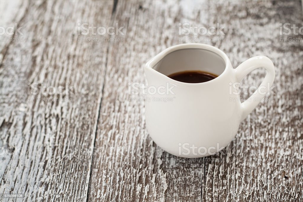 white gravy boat on a rustic wooden background stock photo