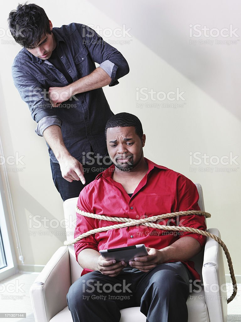 White Guy Forcing Rope Torture Black Guy To Learn Computer stock photo