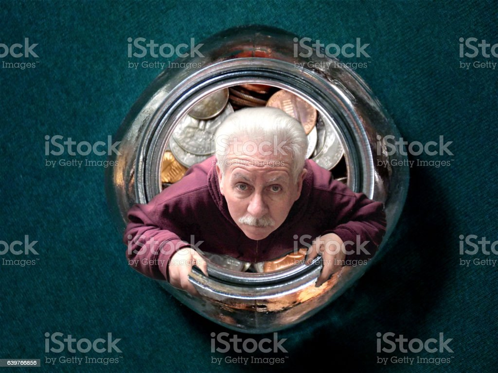 White Haired Man Trapped Inside His Glass Money Jar stock photo