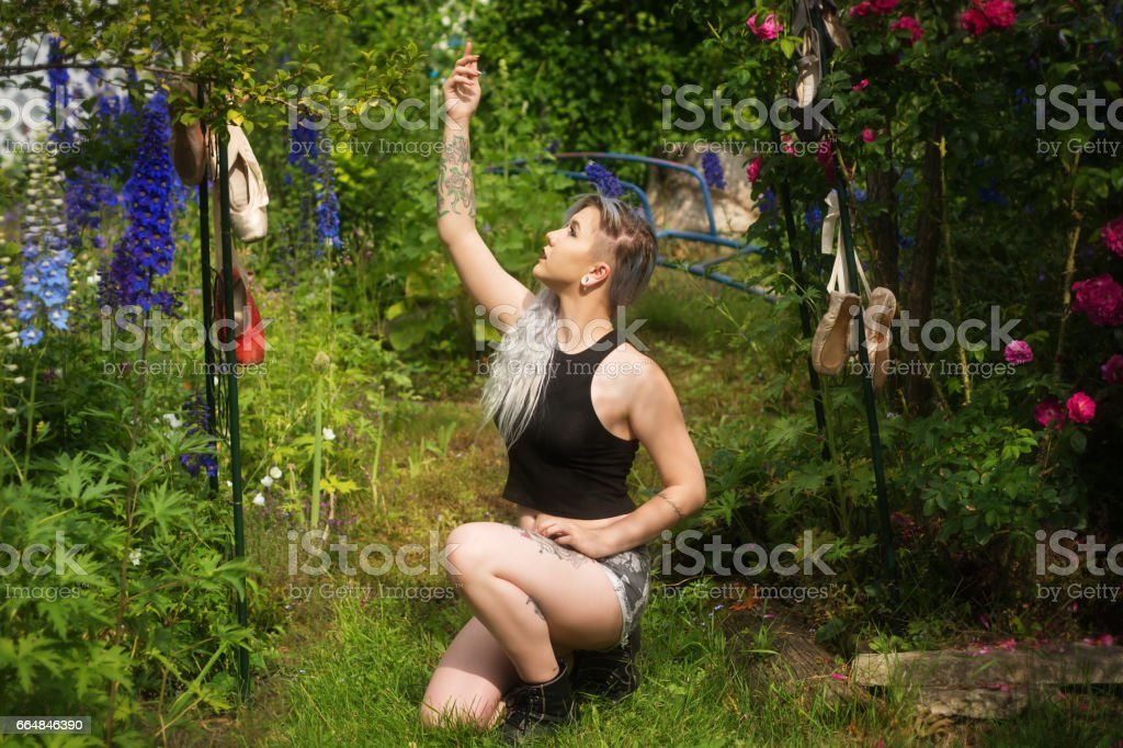 White haired young woman crouching in garden, reaching up to hanging ballet shoes. stock photo