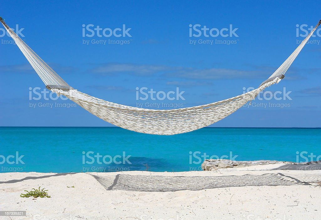 White hammock over a white sand beach with bright blue sky royalty-free stock photo