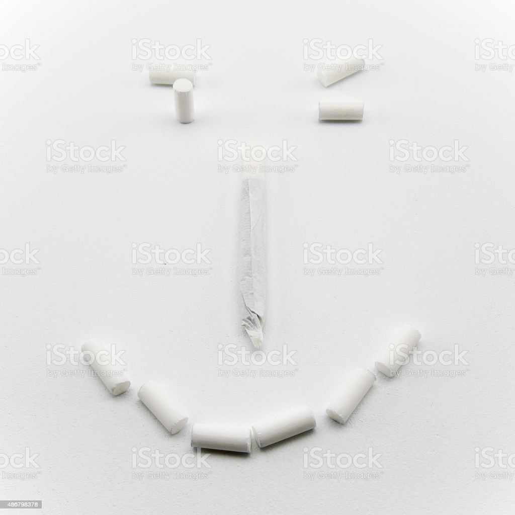White hand made cigarette and filters are smiling. stock photo