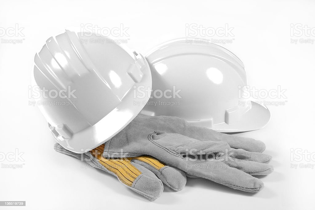 White hard hat with work gloves stock photo