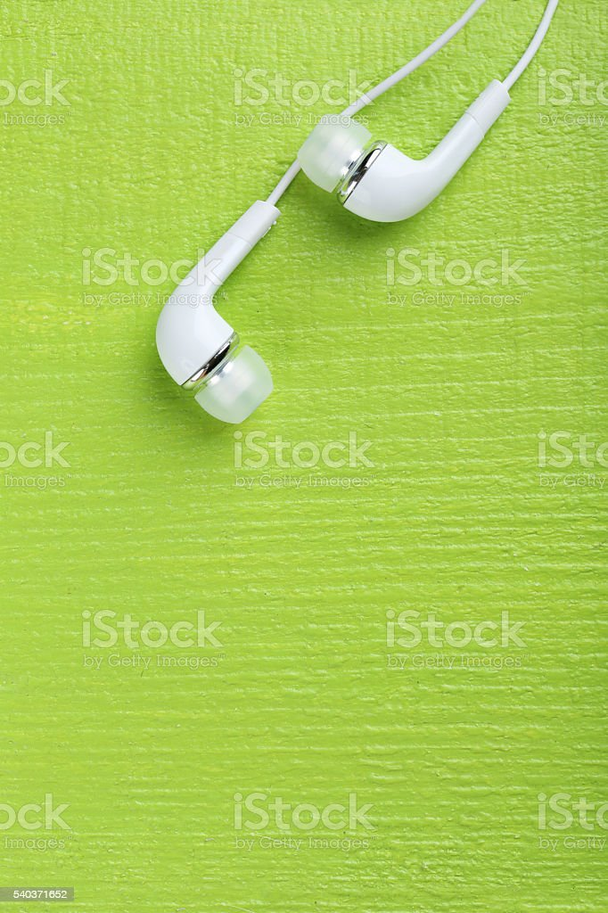 White headphones on a green wooden table stock photo