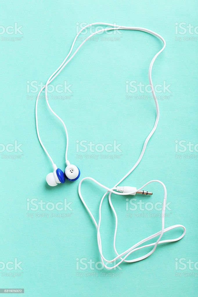 White headphones on a mint paper background stock photo